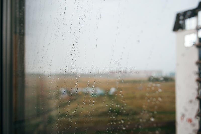 Dramatisches Foto bei Regen: unscharfe Aussicht durch ein Glasfenster mit Wassertropfen Herbst, depressive, regnerische Wetterbed stockfotos