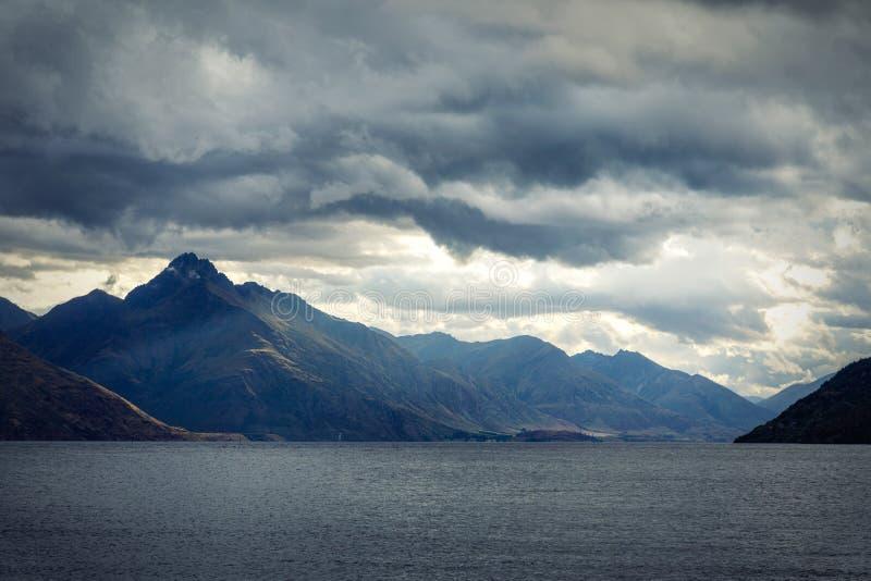 Dramatisk aftonhimmel över bergen och sjön Wakatipu arkivfoto