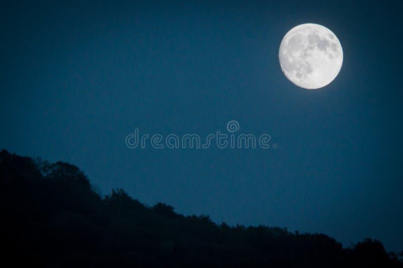 Dramatisk bergmånelöneförhöjning med djupblå nattetidhimmel och i lager kullar i avståndet royaltyfri fotografi
