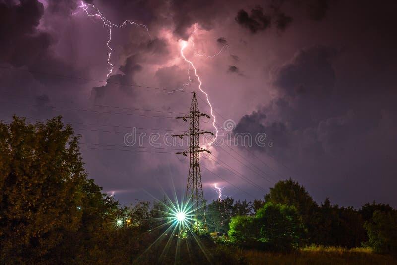 Dramatisk blixt över den höga spänningspylonen royaltyfri foto