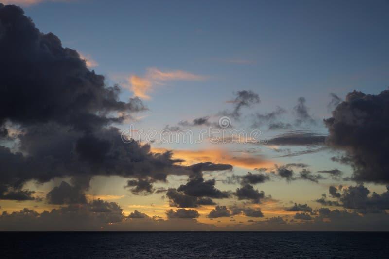 Dramatisk cloudscape under soluppgång över havsvatten royaltyfria bilder