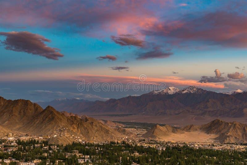 Dramatisk färgrik solnedgång med bergräkningen med snö och den lilla staden nedanför dramatisk mulen himmel royaltyfri fotografi