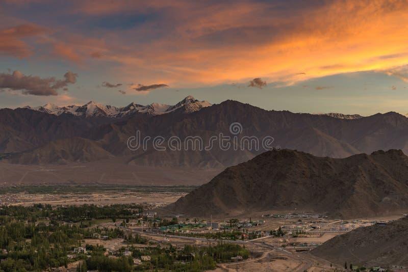 Dramatisk färgrik solnedgång med bergräkningen med snö och den lilla staden nedanför dramatisk mulen himmel arkivbilder