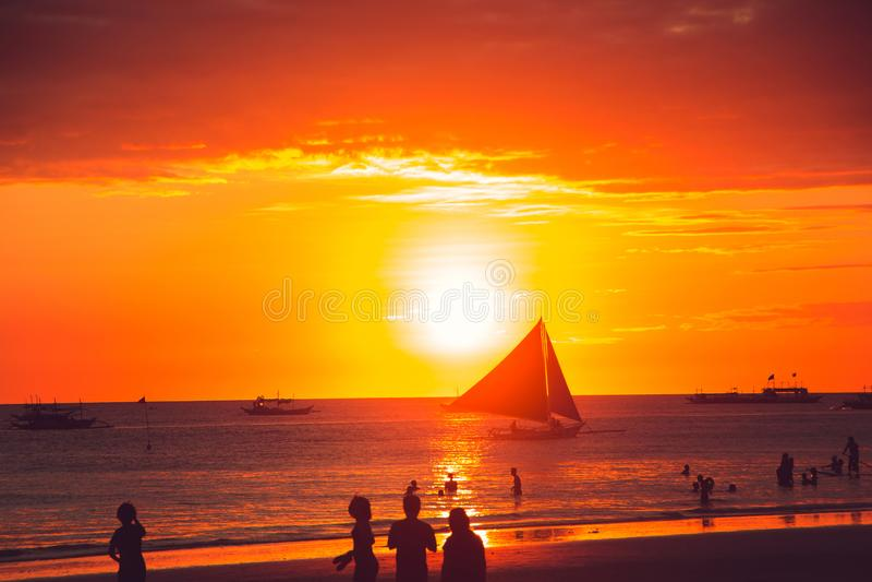 Dramatisk guld- havssolnedgång med segelbåten unga vuxen människa Lopp till Filippinerna Lyxig tropisk semester Boracay paradisö royaltyfri fotografi