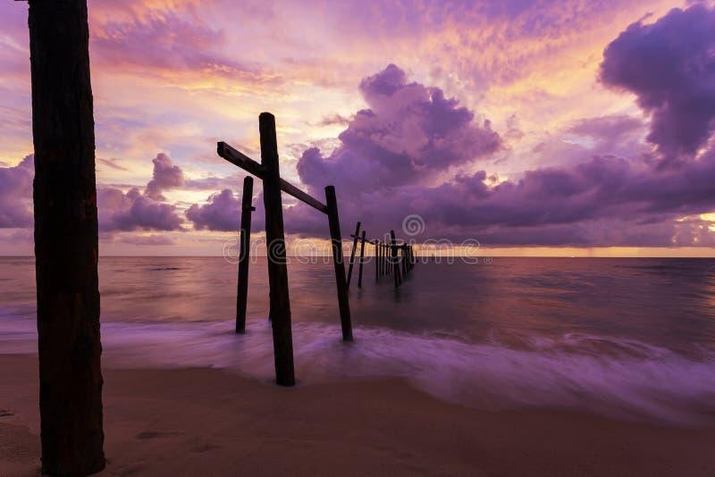 Dramatisk himmel f?r h?rlig solnedg?ng ?ver havet med den gamla tr?bron p? Khao Pilai i Phang Nga Thailand royaltyfria foton