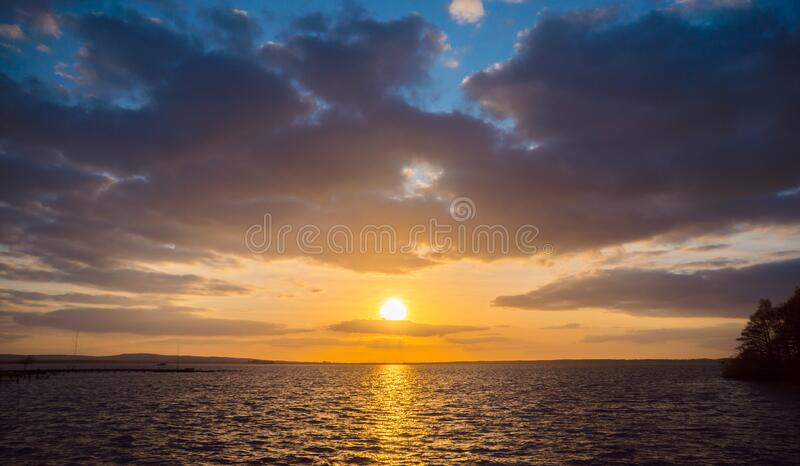 Dramatisk himmel under solnedgång över havet royaltyfria bilder