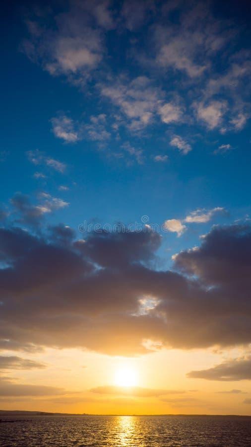 Dramatisk himmel under solnedgång över havet royaltyfri bild