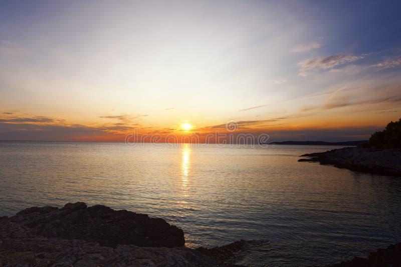 Dramatisk himmel vid solnedgång nära havet fotografering för bildbyråer