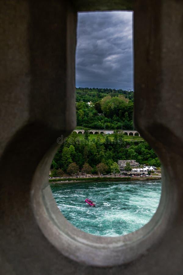 Dramatisk keyhole view of Rhein Rhine water fall in switzerland, bakgrunden har grön skog och dramatisk grumlig himmel arkivbild