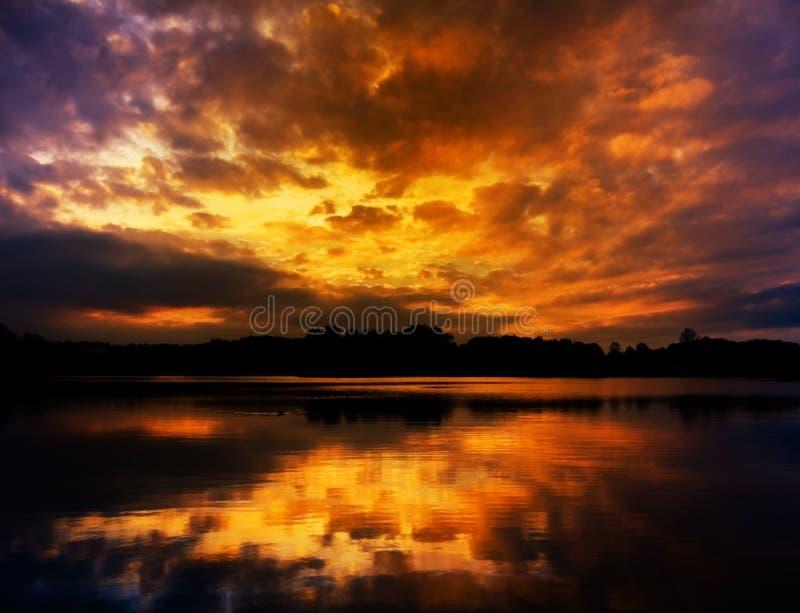 Dramatisk molnig solnedgånghimmelreflexion på sjön arkivbild
