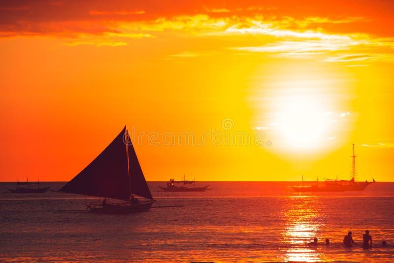 Dramatisk orange havssolnedgång med segelbåten unga vuxen människa Lopp till Filippinerna Lyxig tropisk semester Boracay paradisö royaltyfri bild