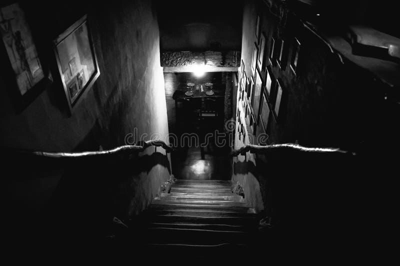 Dramatisk punkt av sikten av trappa från översida in i mörker av inre av den gamla baren arkivbild