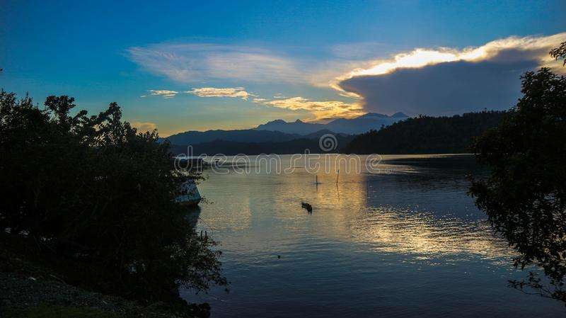 Dramatisk sikt av solnedgången med berghavsbakgrund fotografering för bildbyråer