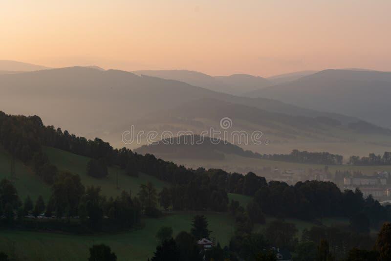 Dramatisk sikt i bergen för stormen - skurkrollgrå färgmoln svävar över gröna bergkanter royaltyfria foton