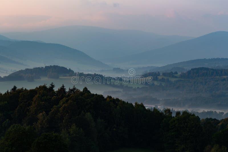 Dramatisk sikt i bergen för stormen - skurkrollgrå färgmoln svävar över gröna bergkanter royaltyfri fotografi
