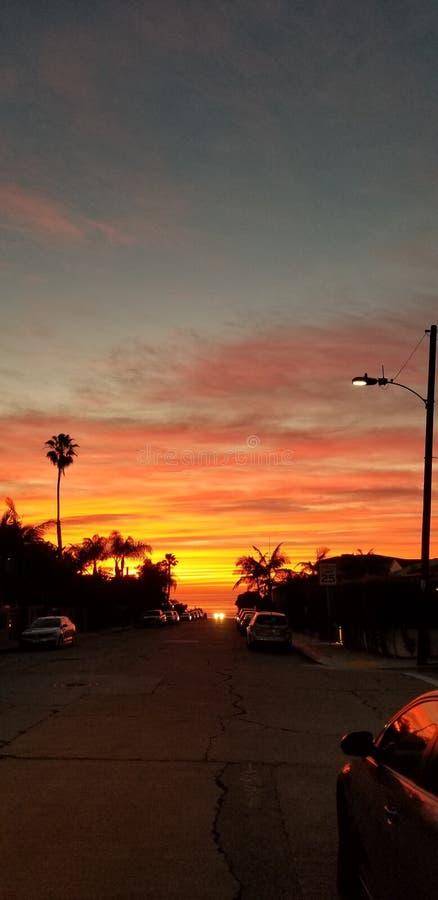 Dramatisk solnedgång över Stilla havet - gatasikten med gömma i handflatan royaltyfri bild