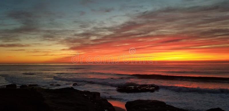 Dramatisk solnedgång över Stilla havet - vågor som kraschar på, vaggar arkivbilder