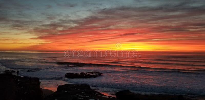 Dramatisk solnedgång över Stilla havet - vågor som kraschar på, vaggar arkivfoto