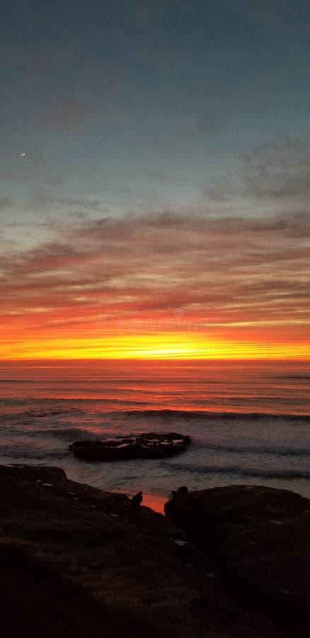 Dramatisk solnedgång över Stilla havet - vågor som kraschar på, vaggar royaltyfria bilder