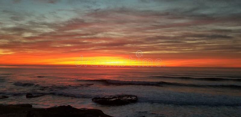 Dramatisk solnedgång över Stilla havet - vågor som kraschar på, vaggar royaltyfri fotografi
