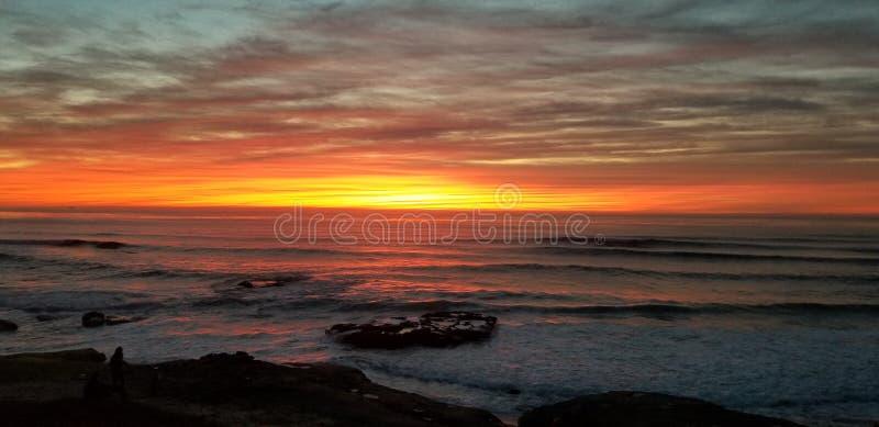 Dramatisk solnedgång över Stilla havet - vågor som kraschar på, vaggar royaltyfria foton