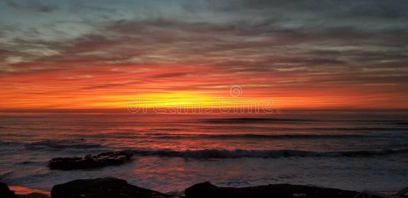 Dramatisk solnedgång över Stilla havet - vågor som kraschar på, vaggar royaltyfri foto