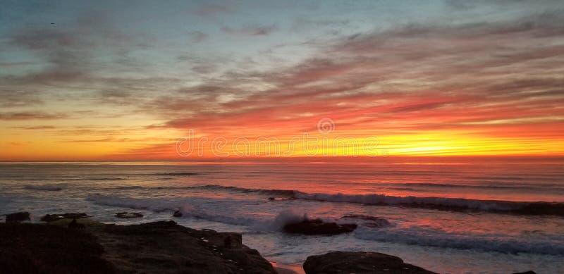 Dramatisk solnedgång över Stilla havet - vågor som kraschar på, vaggar royaltyfri bild
