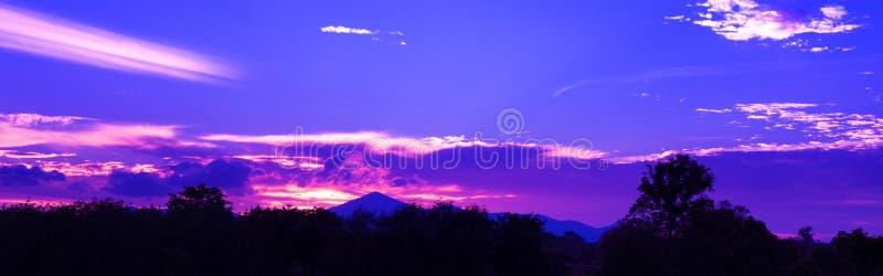 Dramatisk solnedgång för panorama i härligt färgrikt för himmel som har solljus - blått - skymning t för skogsmarken för trädet f royaltyfria bilder