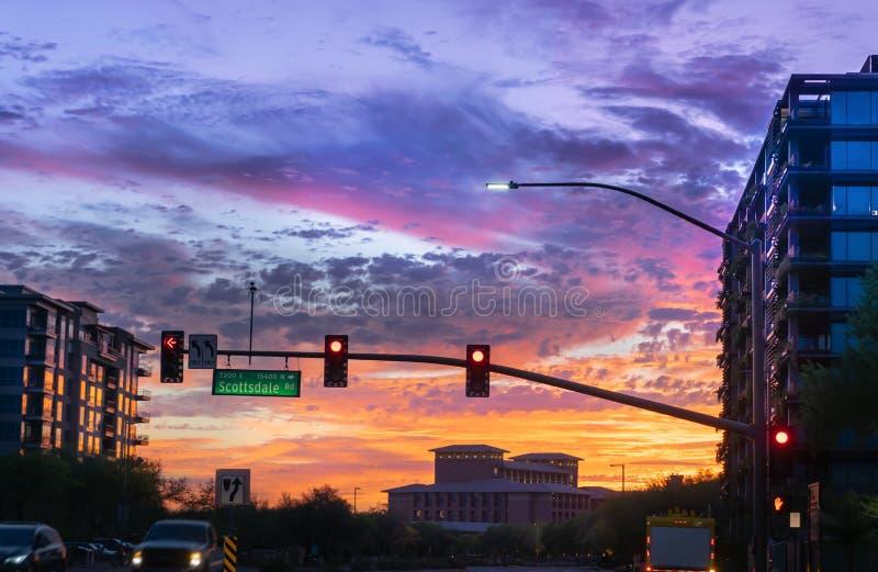 Dramatisk solnedgång i norr Scottsdale, Arizona Bilar kör förbi en upptagen genomskärning på Scottsdale rd och den Kierland blvde arkivbild