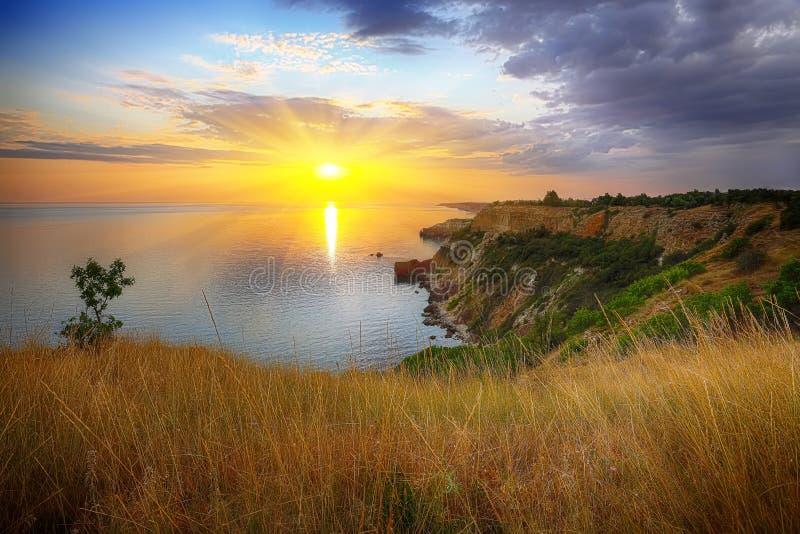 Dramatisk solnedgång på udde Fiolent med busken och gräs på foregroun royaltyfri fotografi
