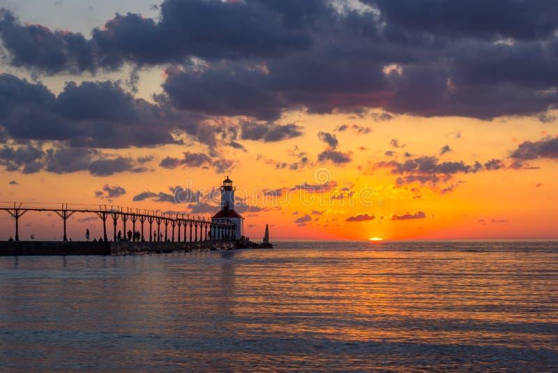 Dramatisk solnedg?ng p? den ?stliga Pierhead f?r Michigan stad fyren fotografering för bildbyråer
