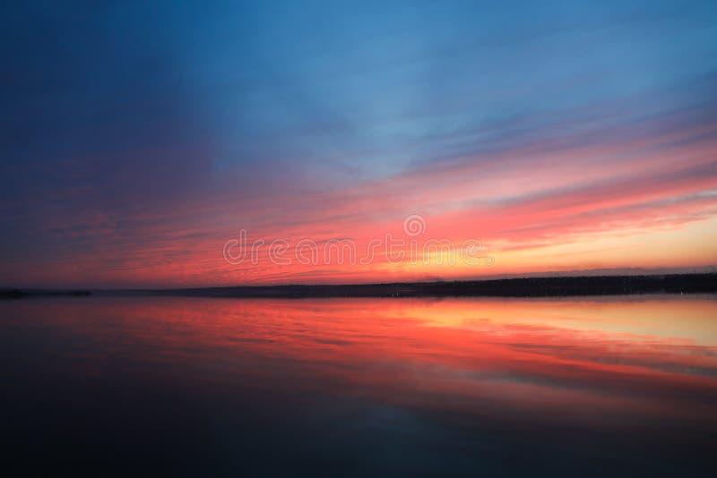 Dramatisk solnedg?nghimmelbakgrund med floden, br?nnhet gul, orange och rosa f?rg f?r moln, naturbakgrund fotografering för bildbyråer