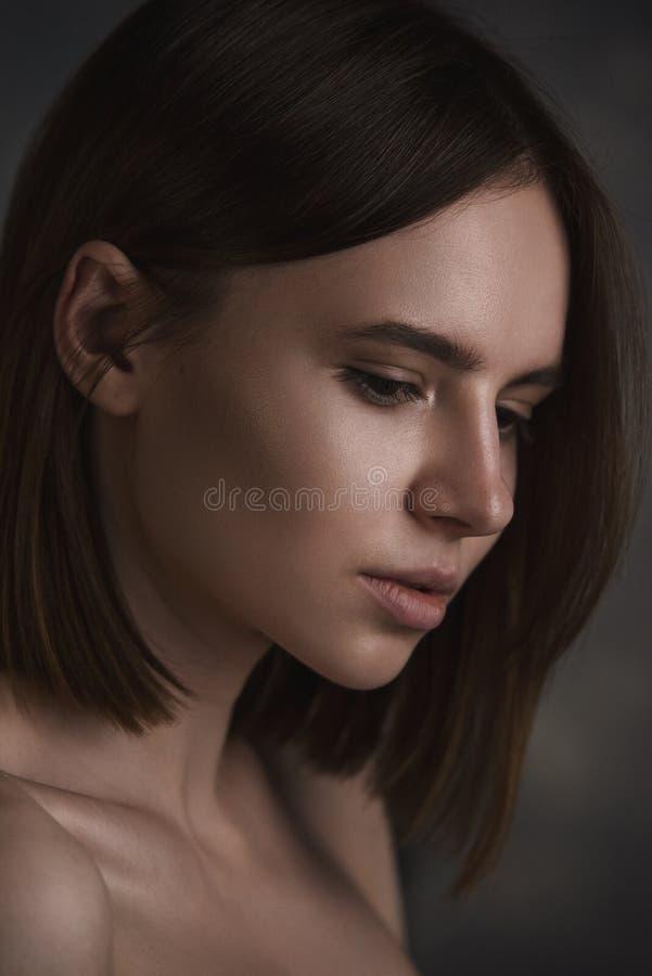 Dramatisk stående av en ung härlig brunettkvinna med kort frisyr i studion royaltyfri bild