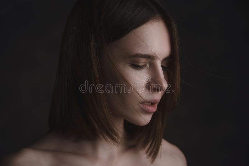 Dramatisk stående av en ung härlig brunettkvinna med kort frisyr i studion royaltyfria bilder