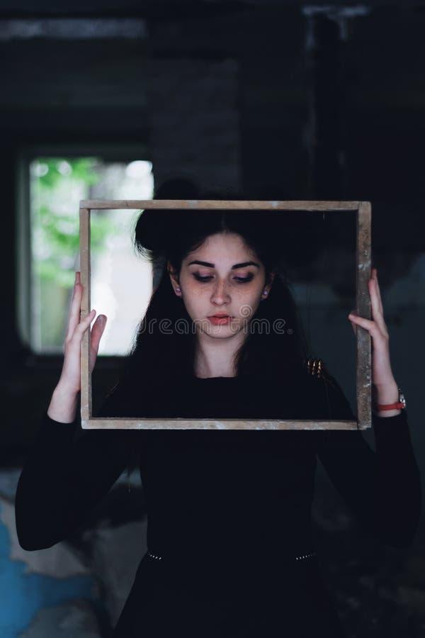 Dramatisk stående av en ung härlig flicka En flicka med ett angenämt utseende och en ledsen blick Idérik stående av en kvinna til royaltyfri bild