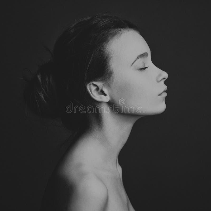 Dramatisk stående av ett flickatema: stående av en härlig flicka på en mörk bakgrund i studio arkivfoto