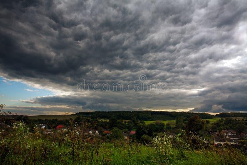 Dramatisk stormhimmel ovanför stormigt väder för by och för skog royaltyfri foto