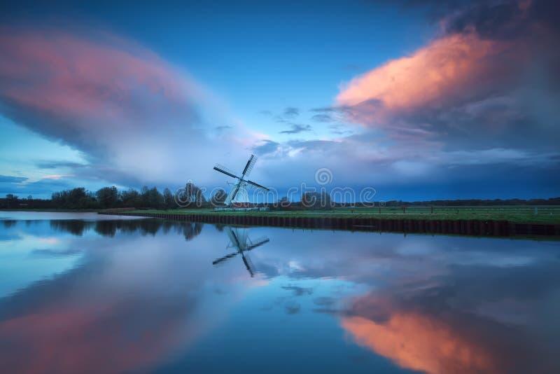 Dramatisk stormig solnedgång över den holländska väderkvarnen och floden fotografering för bildbyråer