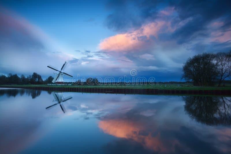 Dramatisk stormig solnedgång över väderkvarnen vid floden fotografering för bildbyråer