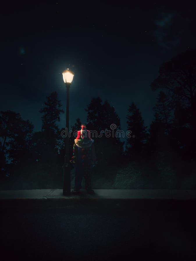 Dramatisk tänd bild av en clown förutom en lampstolpe på natten arkivbilder