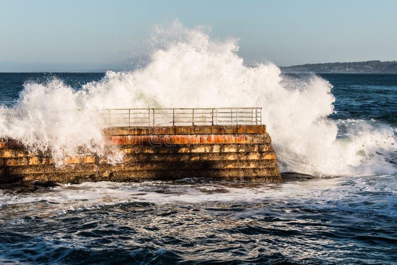 Dramatisk våg som kraschar över barns pölskyddsmur mot havet royaltyfri foto