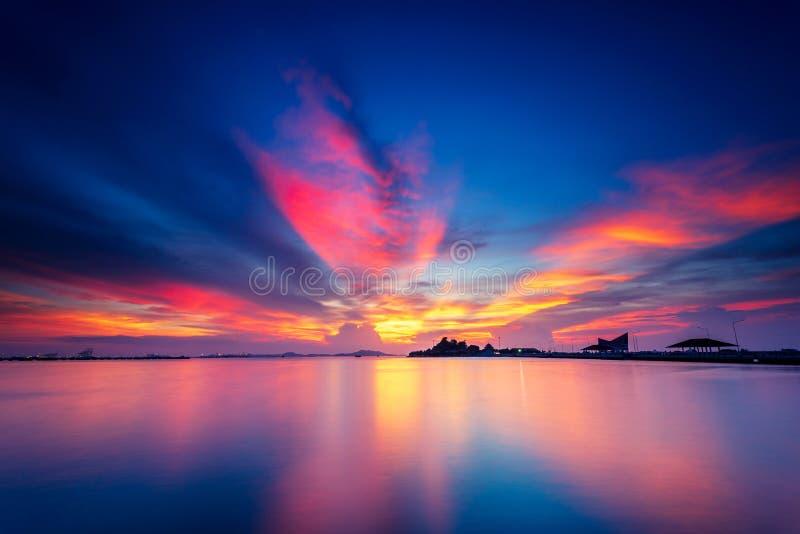 Dramatiska apelsin- och rosa färgstackmolnmoln i solnedgång med blå himmel över ön med yttersida för lugna och plant vatten, himm royaltyfri bild