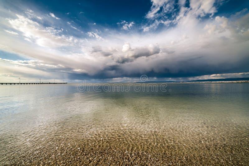 Dramatiska blå himmel och moln över havet arkivbild