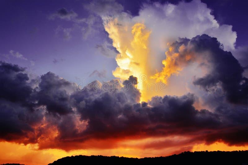 Dramatiska mörka lilor och röda stormmoln på solnedgången arkivfoton