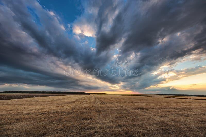 Dramatiska moln över fältet efter skörd royaltyfria bilder
