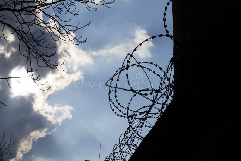 Dramatiska moln bak försett med en hulling - trådstaket på fängelseväggen royaltyfria foton