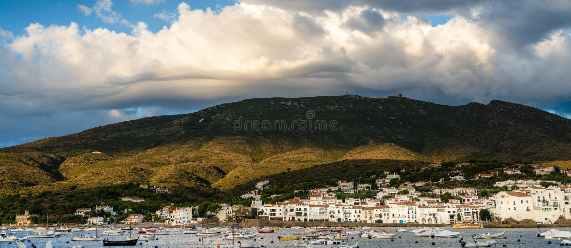 Dramatiska moln bildar över kullarna ovanför fjärd- och sjösidastaden av Cadaques, Girona, Catalonia, Spanien Fartyg som förtöjas royaltyfria bilder