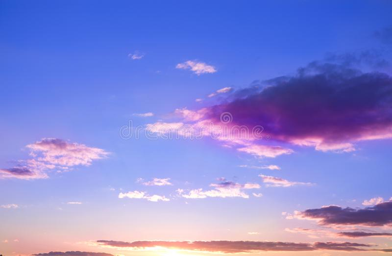 Dramatiska och lynniga rosa färger, lilor och blå molnig solnedgånghimmel arkivbild