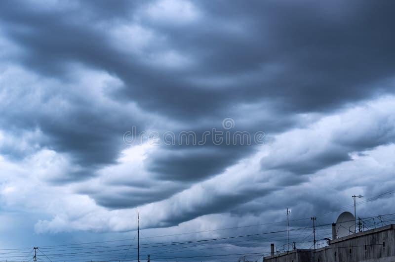 Dramatiska stormiga moln över höghustaket med kabeltrådar, TVantenner och en satellit- maträtt Väder åskväder, royaltyfri bild