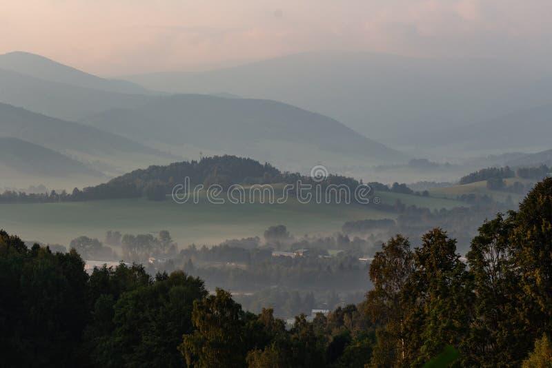 Dramatiskt berglandskap för stormen - skurkrollgrå färgmoln svävar ovanför de gröna skogsbevuxna kullarna till horisonten royaltyfria bilder